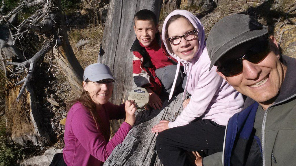 Finding a geocache with my husband and children at Pioneer Cabin